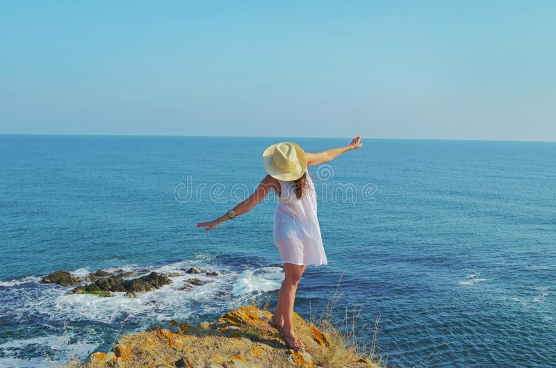 Young Beautiful Boho Style Woman on a Sea Background. Brunette beautiful woman with white dress on the Sea .Summer vacation concept royalty free stock photo