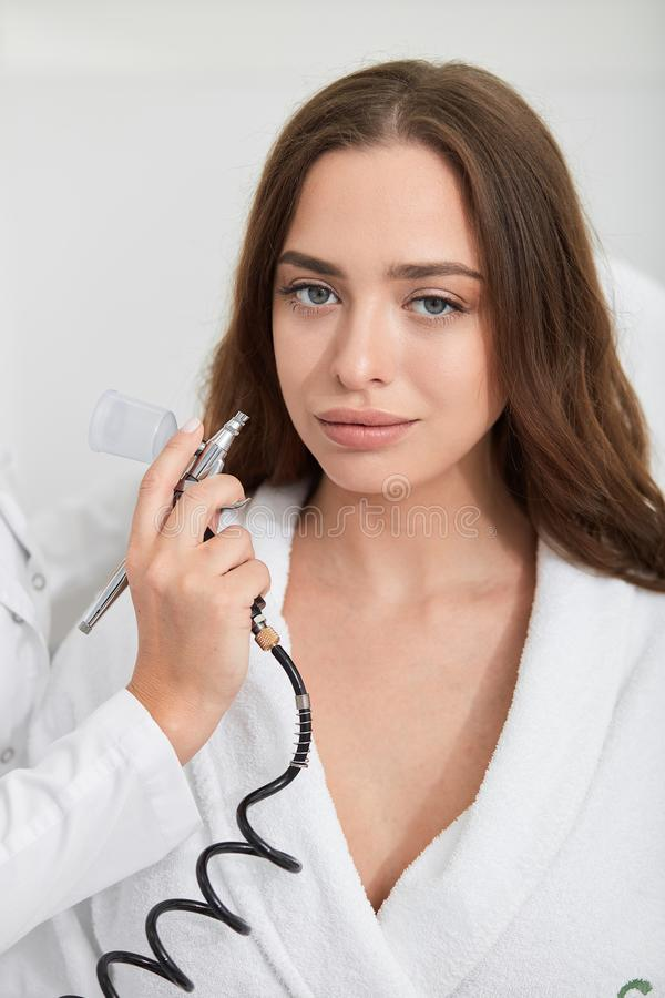 Brunette beautiful young woman spending time in the cosmetological clinic stock image