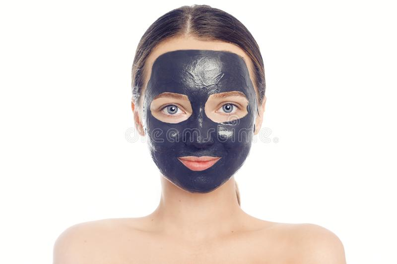 Brunette in a black mask for the face. Beautiful photo of a girl with perfect skin. A young girl cares for herself royalty free stock images