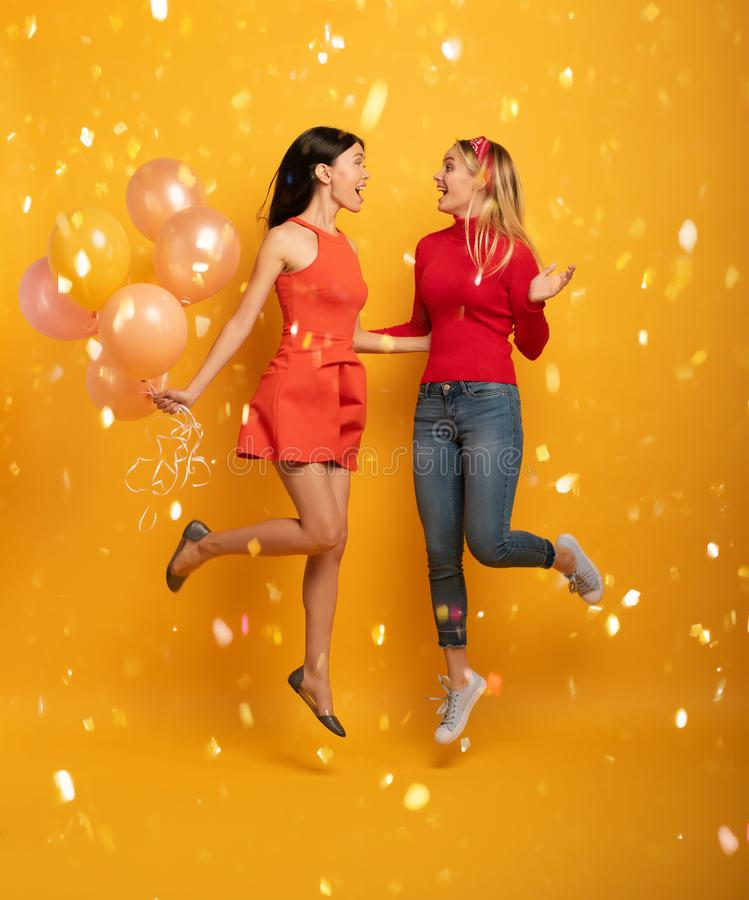 Girls ready for a party with balloons. Joyful an happiness expression. Yellow background royalty free stock images