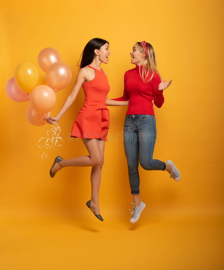Girls ready for a party with balloons. Joyful an happiness expression. Yellow background. Brunette and blonde girls are ready for a party with balloons. Joyful royalty free stock images