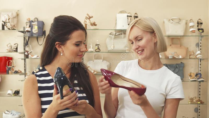 Two women comparing shoes in shoe shop stock photos