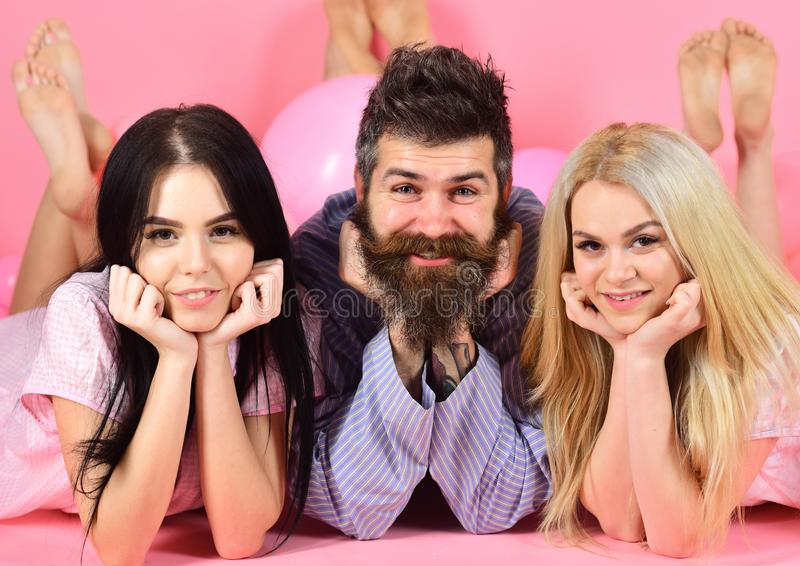Brunette and blonde in love with bearded hipster. Women in pink pajamas posing on camera while lay with bearded macho in stock photos