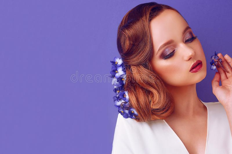 Brunette on a blue background. Girl with professional make-up and hairstyle. Beauty salon. Girl with blue flowers in her hair. stock image