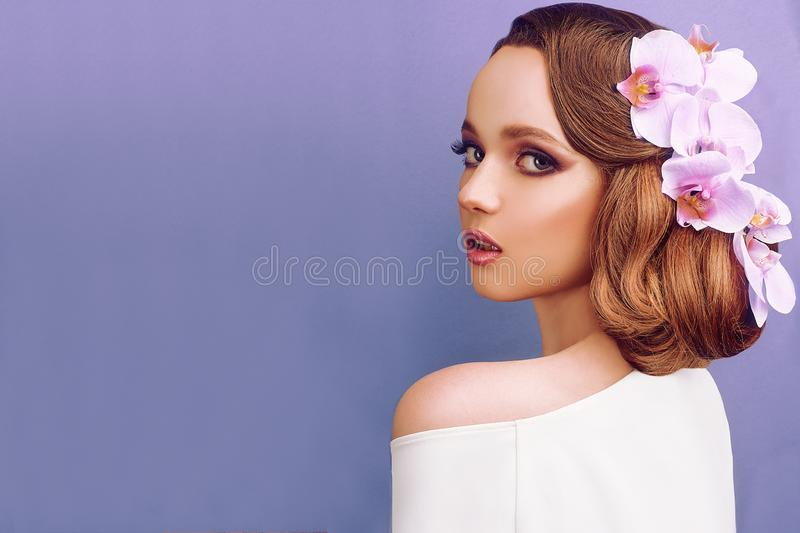 Brunette on a blue background. Girl with professional wedding make-up and hairstyle. Beauty salon. Wedding hairstyle, purple. Makeup. Flower shop. Pink orchid stock images
