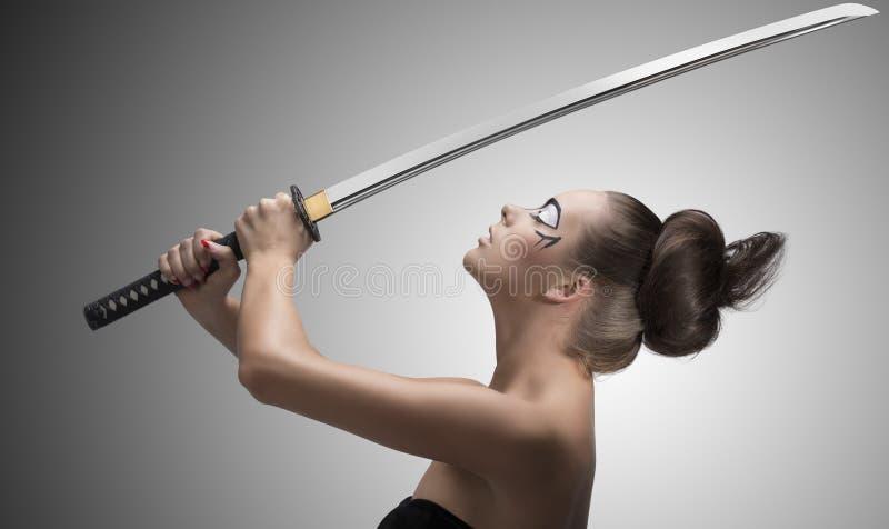 O Brunette no estilo de japão com katana taked com ambas as mãos imagens de stock royalty free