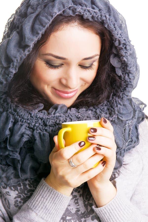 Brunette bonito com um copo amarelo do chá quente foto de stock