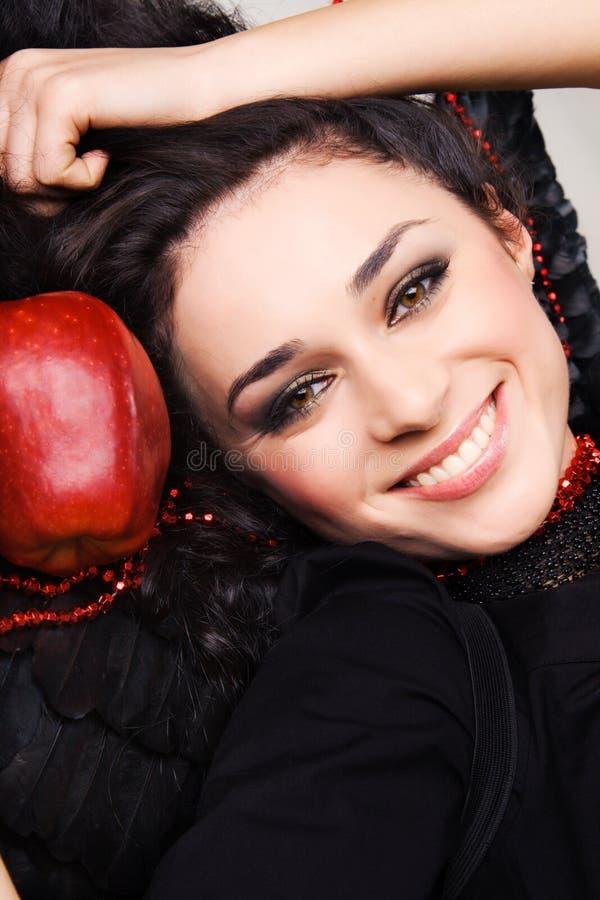 Brunette bonito feliz com uma maçã vermelha grande imagem de stock