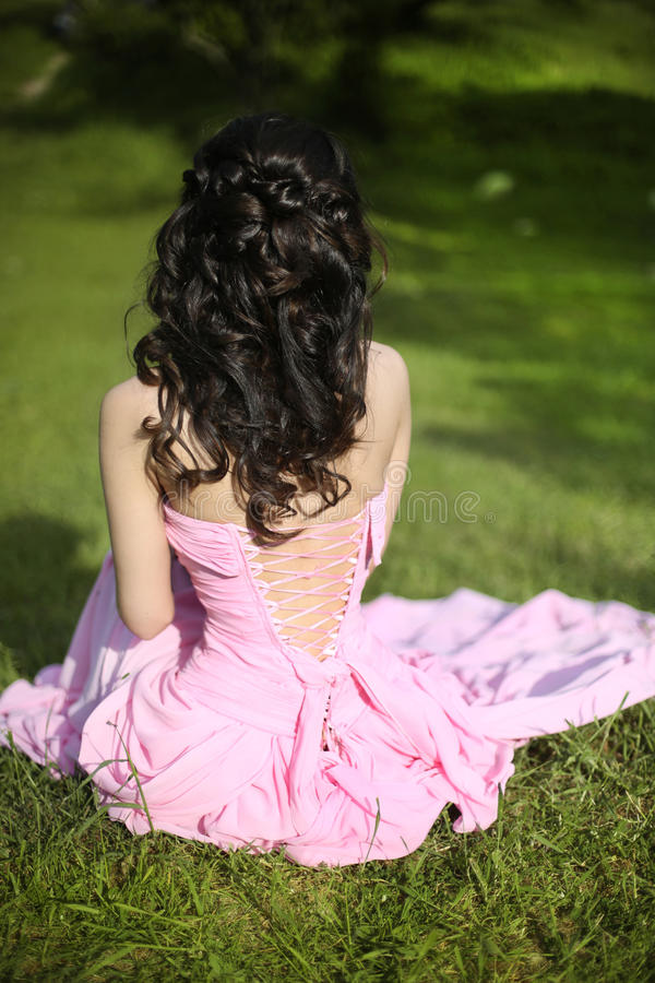 Brunette bride resting and sitting on green grass at spring park. Beauty portrait stock photo