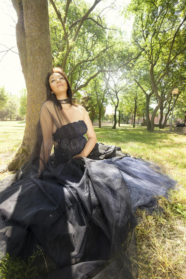 Brunette bride woman wedding blue dress sitting near tree stock photos
