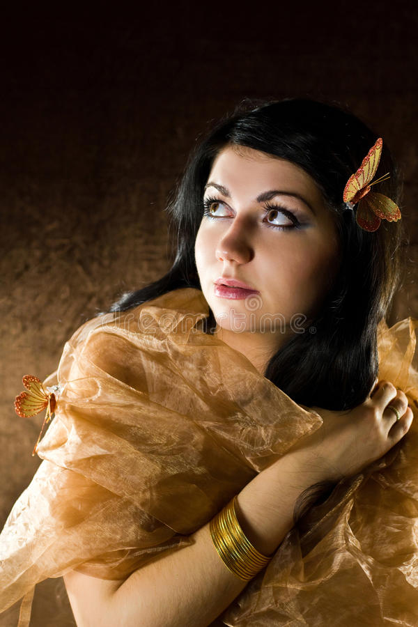 Brunette with brown-gold butterfly stock photo