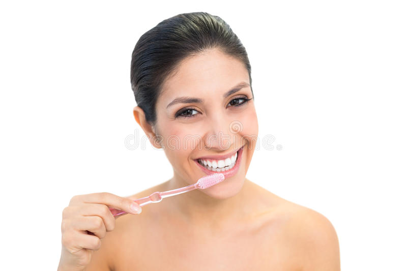 Brunette brushing her teeth and smiling at camera stock images