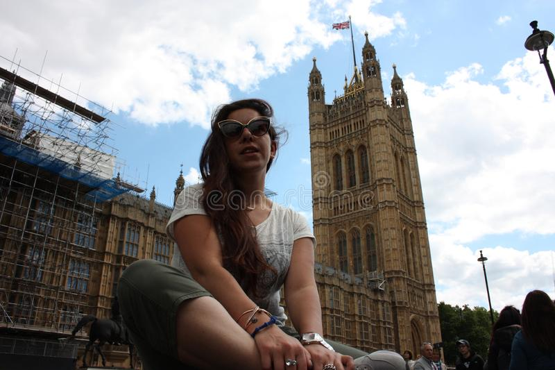 Brunette Caucasian tourist girl resting sitting under the seat of two houses of parliament in Westminster in London.  stock photo