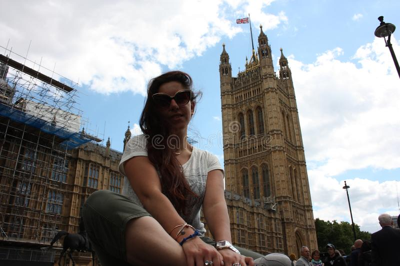 Brunette Caucasian tourist girl resting sitting under the seat of two houses of parliament in Westminster in London.  stock images