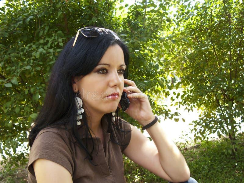 Brunette che comunica sul telefono mobile immagine stock libera da diritti