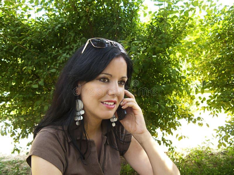 Brunette che comunica sul telefono mobile fotografia stock