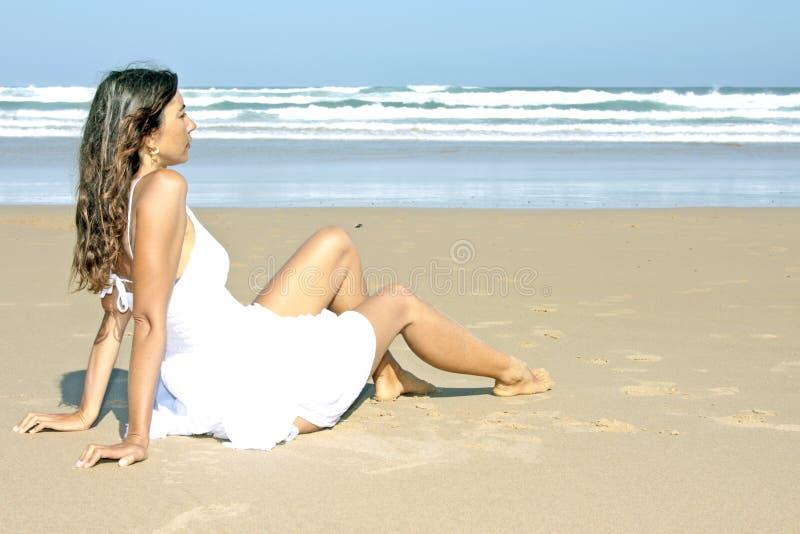 Brunette che si distende alla spiaggia fotografia stock libera da diritti
