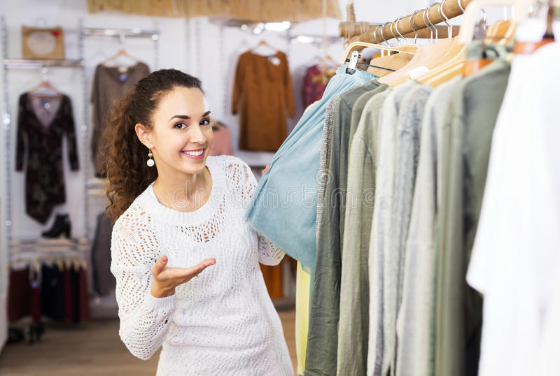 Brunette choosing skirt in shop. Happy young brunette choosing new skirt on hangers in shop stock photography