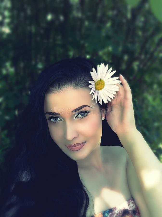 Brunette con i fiori in suoi capelli fotografia stock libera da diritti