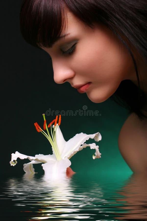 Brunette con las flores del lirio blanco en agua fotos de archivo libres de regalías