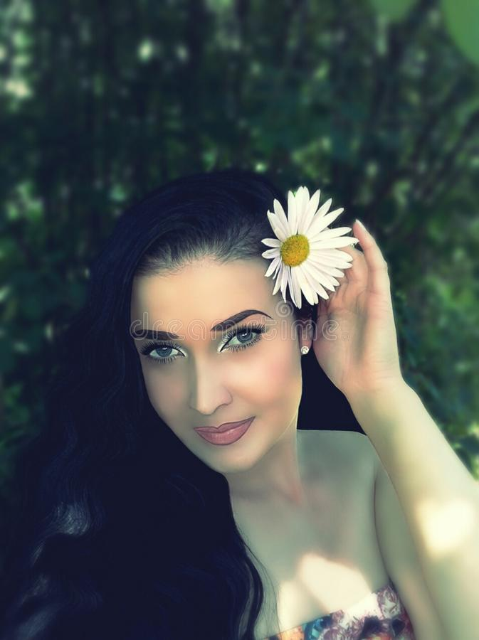 Brunette con las flores en su pelo fotografía de archivo libre de regalías