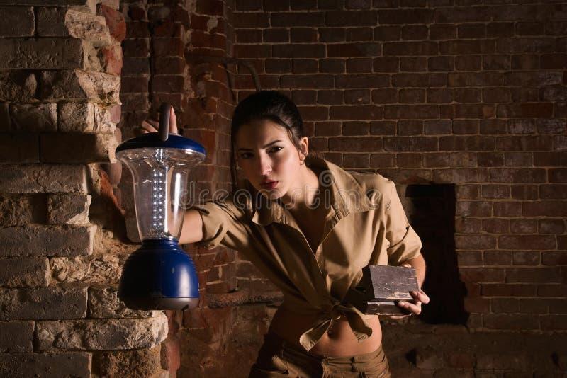 Brunette con un tesoro de la búsqueda de la linterna en las ruinas fotos de archivo libres de regalías