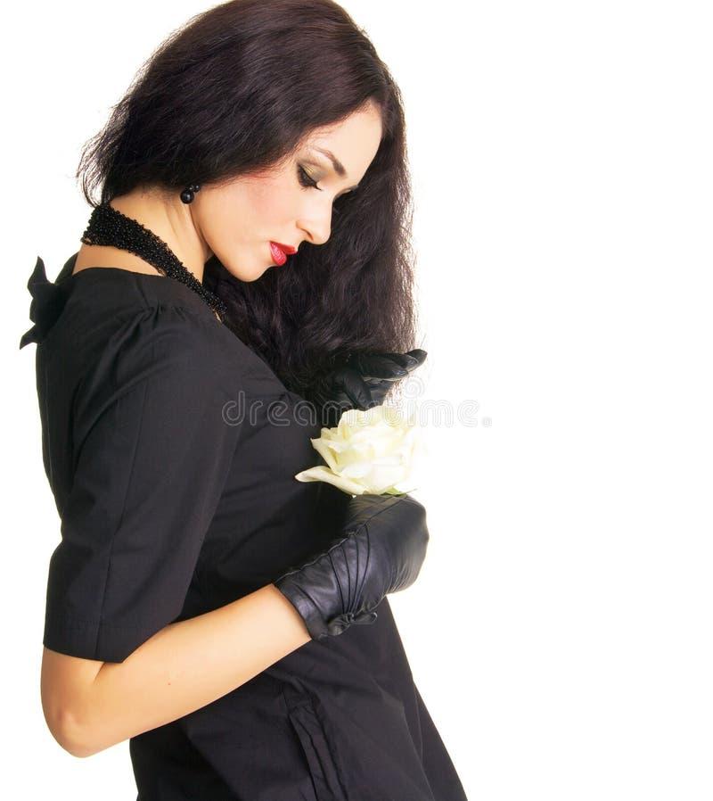 Brunette consideravelmente modesto que prende o botão de uma rosa branca fotos de stock royalty free