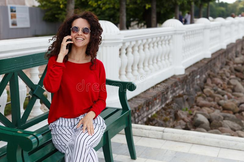 Brunette curly girl, wearing in red and sunglasses, talking on a phone, seated on a wooden bench in park, in sunny day. stock photo