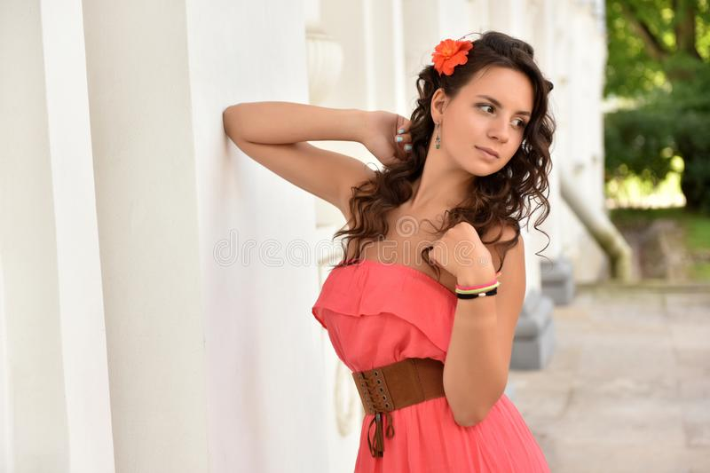 brunette with curly hair in a pink dress royalty free stock images