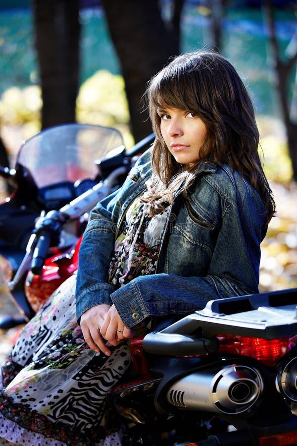 Brunette da menina com uma motocicleta vermelha imagens de stock