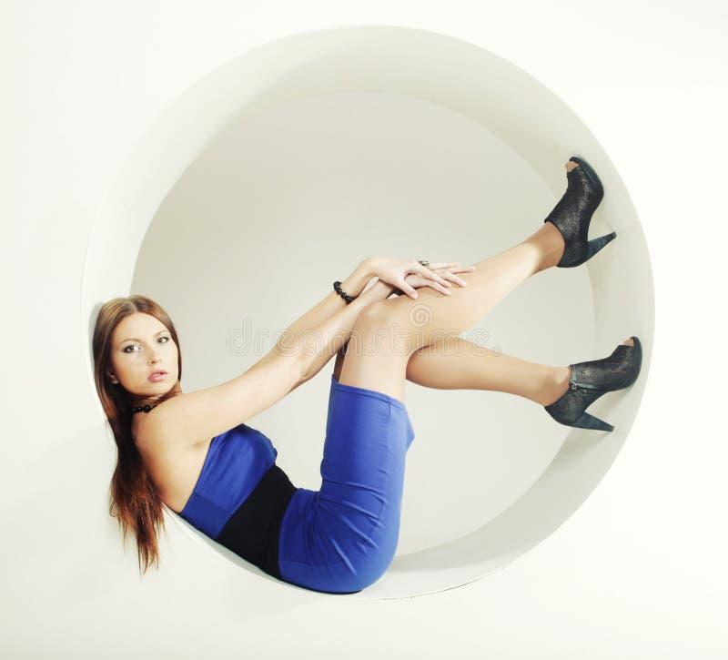 Brunette dans la robe bleue se reposant en cercle photo stock