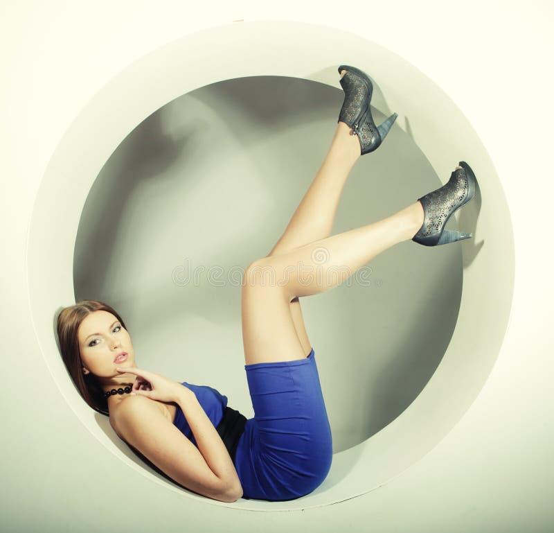 Brunette dans la robe bleue se reposant en cercle photos libres de droits