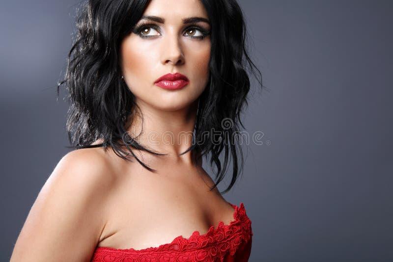 Brunette dans la robe rouge. photos stock