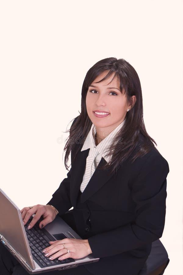 Brunette de Smilling travaillant sur un ordinateur portatif photographie stock libre de droits