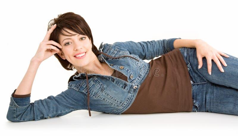Brunette de sorriso bonito que encontra-se para baixo e que relaxa imagens de stock