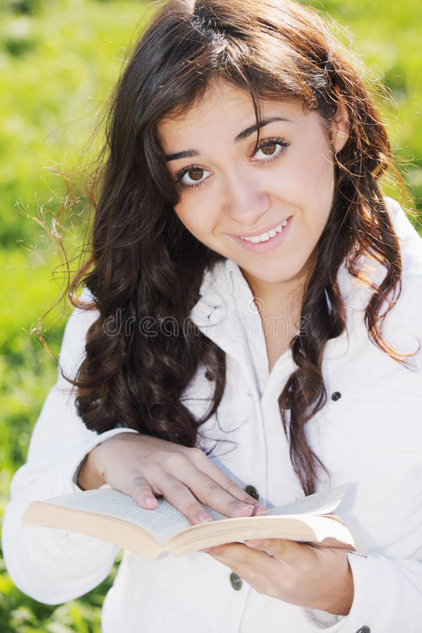 Brunette de sorriso novo no branco com livro foto de stock royalty free