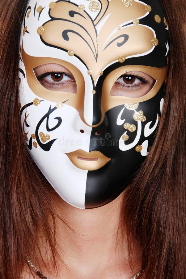 Brunette del primo piano che porta una mascherina nera bianca dell'oro fotografia stock libera da diritti