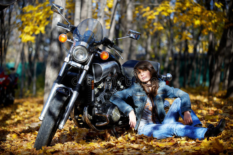 Brunette della ragazza con un motociclo immagini stock libere da diritti