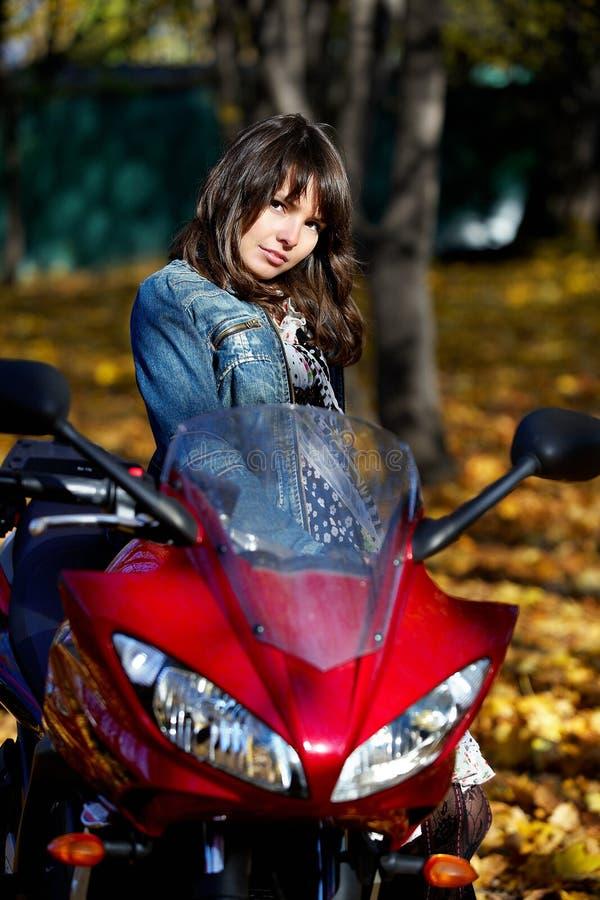 Brunette della ragazza con un motociclo rosso immagini stock libere da diritti