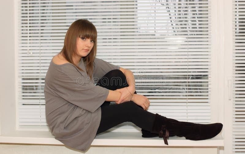 Brunette, der auf dem Fenster sitzt lizenzfreie stockfotos