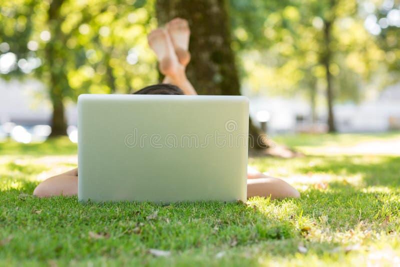 Brunette, der auf dem Gras schreibt an ihrem Laptop liegt stockbilder