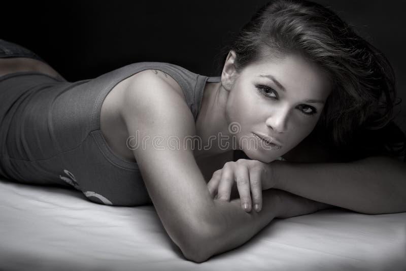 Brunette, der auf ihr Bett legt lizenzfreies stockfoto