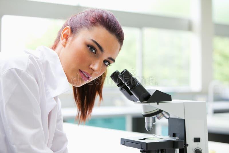 Brunette, der mit einem Mikroskop aufwirft stockbilder