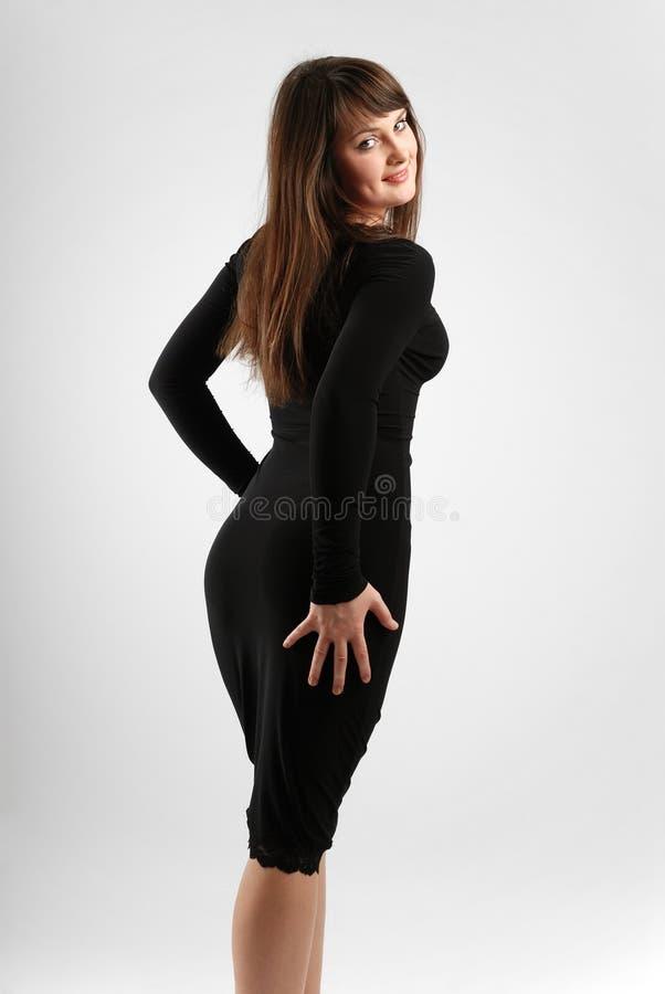 Brunette in der schleichenden schwarzen, hinteren Ansicht stockbild