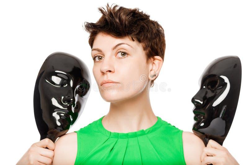 Brunette, der schwarze Maske zwei auf einem weißen Hintergrund hält stockbild