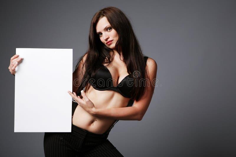 Brunette, der unbelegtes Zeichen anhält. stockbild