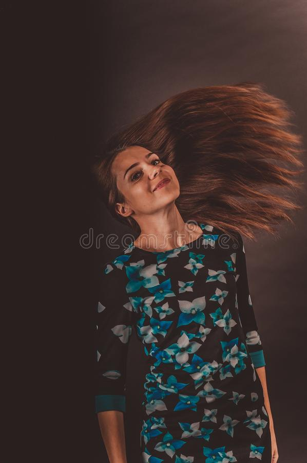 Brunette with developing hair. Photo in the studio on a dark background royalty free stock image