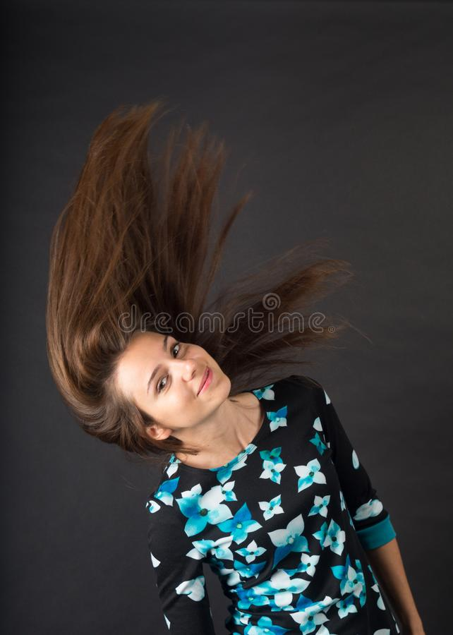 Brunette with developing hair. Photo in the studio on a dark background stock photo