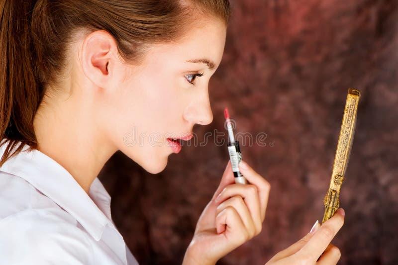 Brunette die lippenstift toepassen stock foto