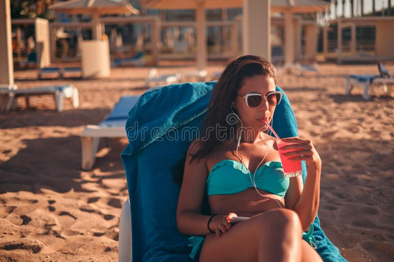 Brunette drinking cocktail and listening music on the beach royalty free stock photo